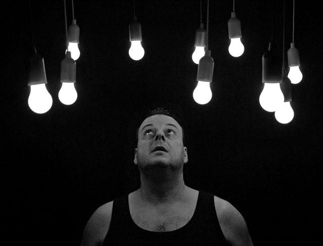 muž sleduje žárovky nad ním