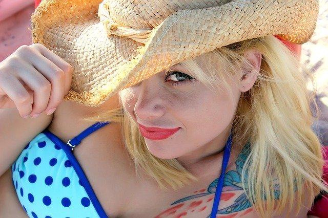 žena v plavkách s kloboukem na hlavě